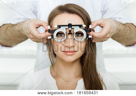ophthalmologist examining attractive woman with optometrist trial frame. female patient to check vision in ophthalmological clinic