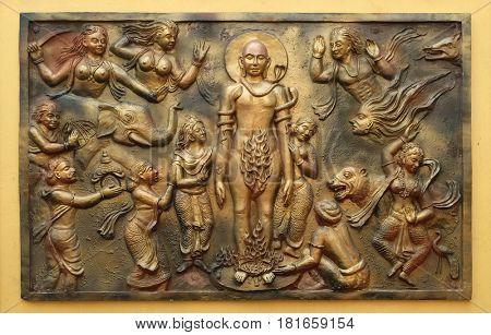 KOLKATA,INDIA - FEBRUARY 09, 2016: Jealous god Sangama tests Mahaviras enderance and, courage by twenty severe tests: Mahavira is victorius, bass relief on the wall of Jain Temple in Kolkata