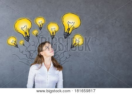 Portrait of thinking young european woman with drawn yellow light bulb balloons on concrete background. Idea concept