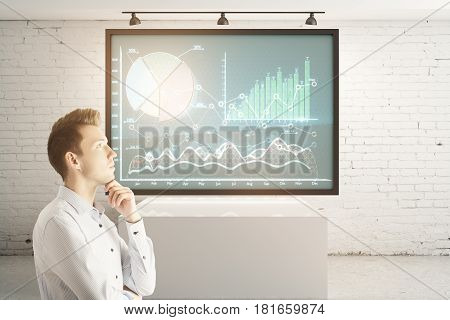 Side portrait of young businessman in interior with digital business charts on poster. Financial growth concept. 3D Rendering
