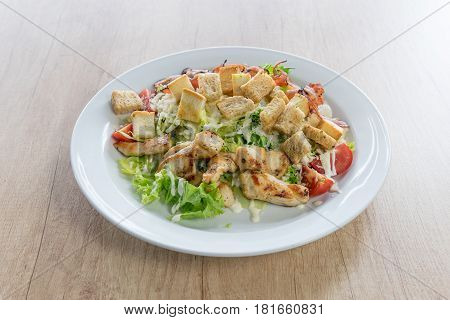 Caesar salad with chicken on the wooden table