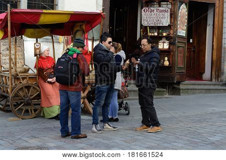 TALLINN, ESTONIA - APRIL 11, 2017: Tourists in Old City in Tallinn. Sellers Scandinavian baked breaded almond nuts with cinnamon, garlic, pepper, sugar in medieval dresses.