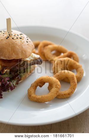 Burger with onion rings on white plate closeup