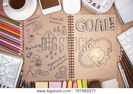 Top view of messy office desktop with sketch in notepad colorful supplies coffee cup electronic devices and other items. Targeting concept
