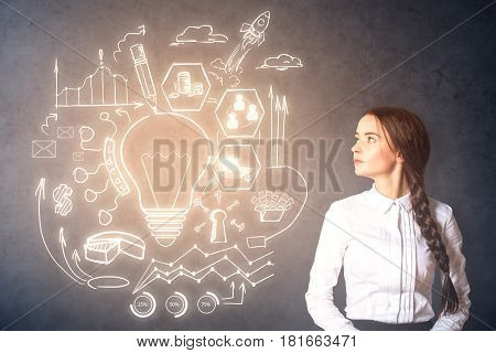 Pondering young woman on chalkboard background with illuminated business sketch. Successful ideas concept