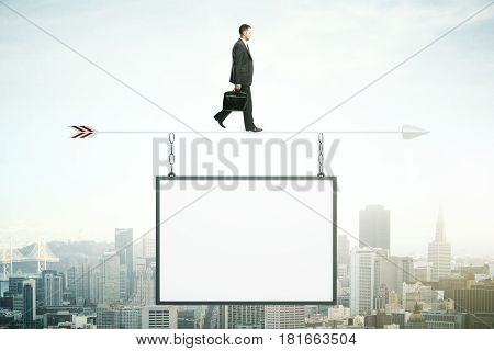 Businessman walking on abstract arrow with suspended empty poster. City background. Mock up. Success concept