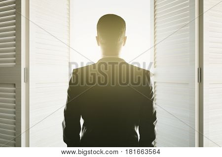 Back view of young man looking at bright light shining from open white doors. Success concept. 3D Rendering
