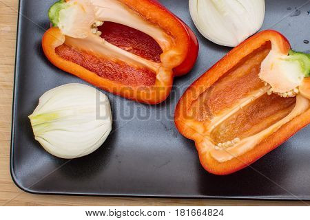 Two halves of red sweet pepper and two halves of onion on a black plate.