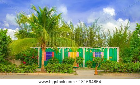 Abandoned container by the roadside painted as a house surrounded by a tropical vegetation in Cayman Islands