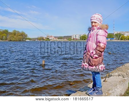 Caucasian schoolgirl on the old concrete dam of water reservoir in cool period of early spring