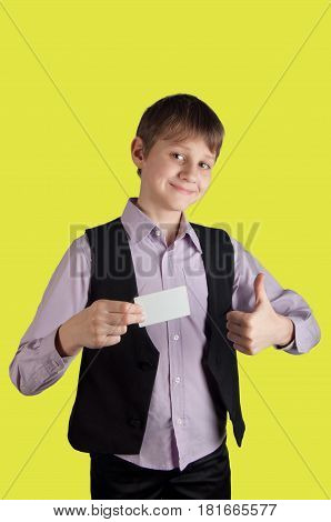 Boy in purple shirt and black waistcoat holding white credit card on yellow background smiling and showing big finger up. Vertical photo