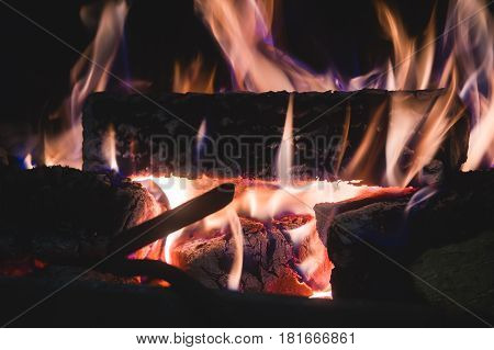 Burning fire with charcoal, firewood and fuel briquette in a fireplace in a country house