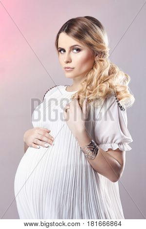 Pregnant woman in white dress on gray background. A few days before birth. Beautiful pregnant blonde woman waiting for the birth of the child. Expectant mother