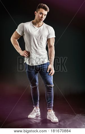 Handsome young muscular man looking at camera in studio shot over neutral background. Full length shot
