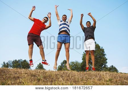 Group of three friends have fun jumping together blue sky background