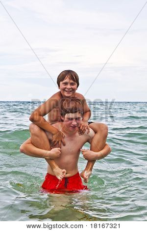 Boys Having Fun In The Beautiful Clear Sea