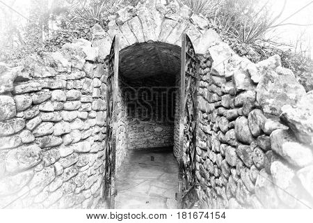 A gated front entrance into a man made replica of a cave made of stone in black and white