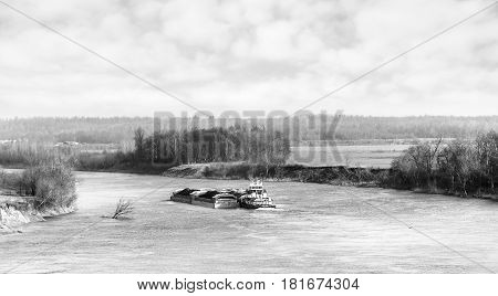 A barge pushing a load of coal down river in a spring rural landscape