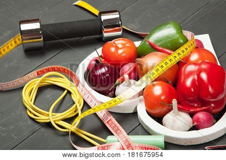 Sport and diet. Healthy lifestyle. Vegetables, dumbbells. Peppers, tomatoes, garlic, onion radish in a heart on black background