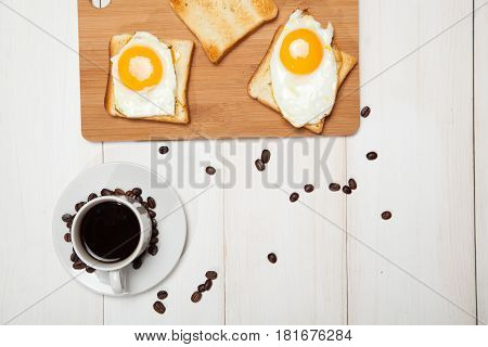 cup of coffee, toast and egg on a white wooden table