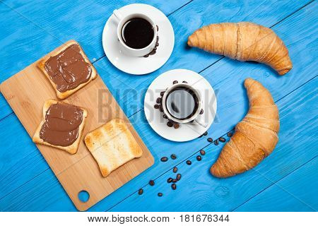 Two cups with coffee, croissant and toast with chocolate on a blue wooden table