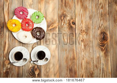 Two cups with coffee and donuts on a wooden background