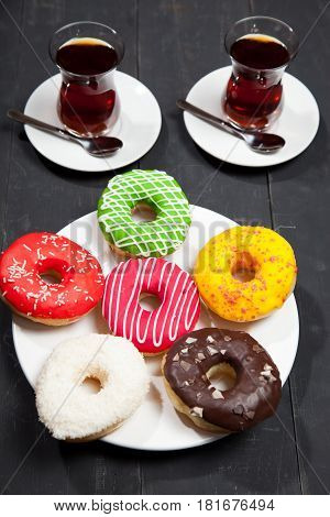 Cups of tea and donuts on a black wooden background