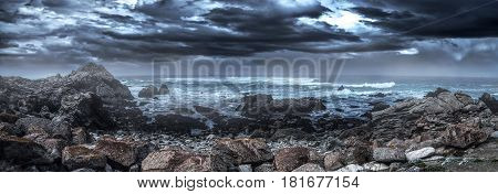 Foggy view of Pebble Beach California coast with storm clouds and rough seas causing waves to crash on rocks. The picture depicts the Pacific Ocean and tourism in Monterey America. The beach is shaped by erosion and climate change.