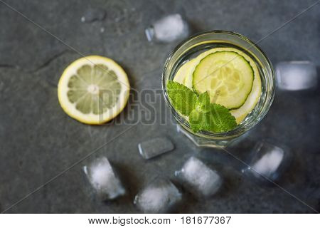 Cool refreshing drink: pure water ice lemon cucumber and mint garnish. Top view