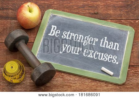 Be stronger than your excuses - fitness concept on a slate blackboard against weathered red painted barn wood with a dumbbell, apple and tape measure