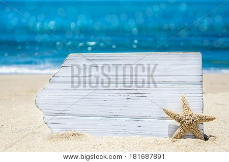 Empty white wood board with starfish on the sandy beach near the ocean