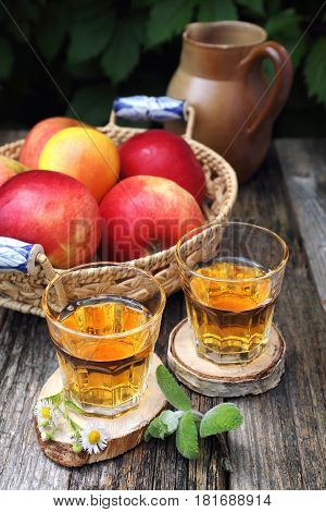 Apple juice in two glass on old wooden table in the garden