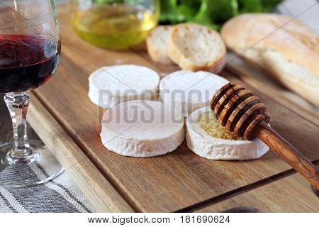 Soft French goat cheese Rocamadour bread honey lettuce and glass of red wine. Focus selective