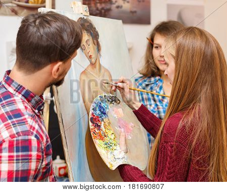 Master class in art school. The teacher draws a portrait with oil paints and students observe the process of execution. Courses of drawing for adults.