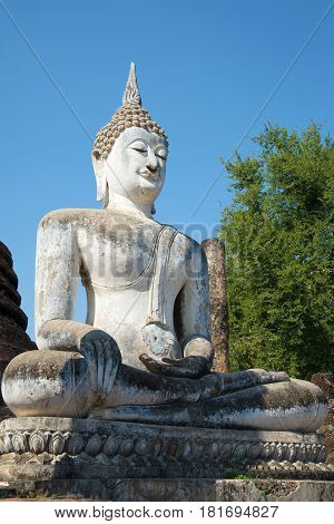 Ancient sculpture of a sitting Buddha close up. Ruins of the Buddhist temple of Wat Sa Si in the Sukhothai. Thailand
