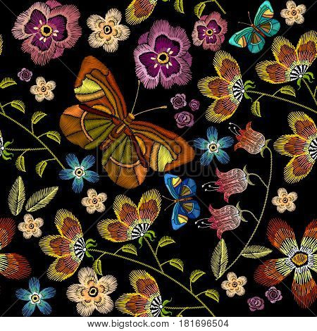 Embroidery flowers and butterflies seamless pattern. Beautiful camomiles cornflowers classical embroidery on black background fashionable template for design of clothes