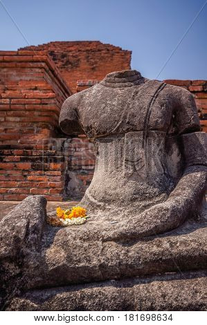 Broken headless Buddha image at Mahathat temple in Ayuthaya historical park Thailand