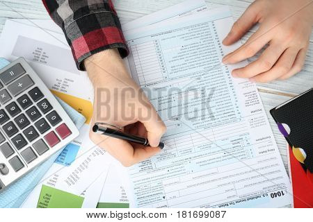 Man filling form of Individual Income Tax Return, closeup