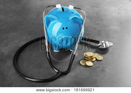 Piggy bank with stethoscope and coins on table