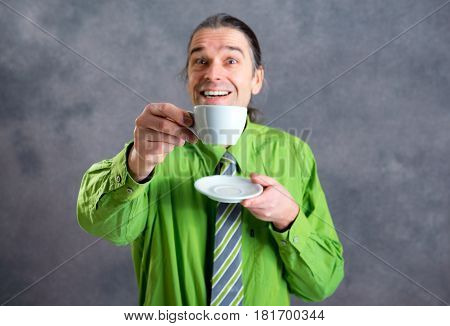 Young Man In Green Shirt And Necktie Drinking Coffee