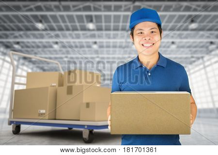 asian delivery man holding boxes in distribution warehouse