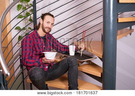 Man In Checkered Shirt Sitting On Stairs And Eating Asian Food
