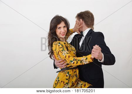 Brunette girl in a yellow dress dancing with a guy in a tuxedo