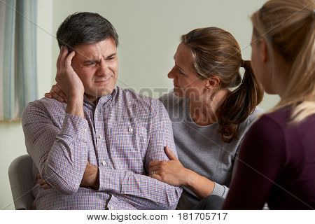Mature Couple Talking With Counsellor As Woman Comforts Man