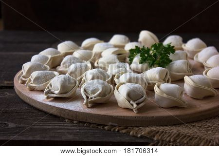 Dumplings raw on a round board. Russian national food. The process of cooking dumplings. Dark background