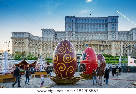 Bucharest, Romania - 15 April, 2017: People walking in front of the famous Parliament building in Easter, where was organized a traditional religious market, Christian celebration holiday