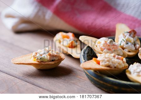Tartlets with spicy salad on a wooden background