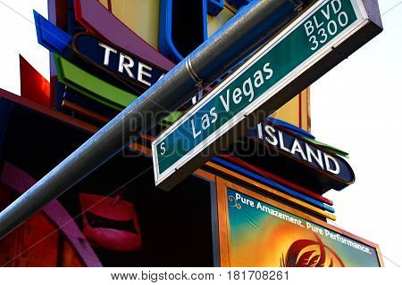 Las Vegas, Nevada, USA - October 9, 2016: View at a Treasure Island casino Las Vegas street sign on the Las Vegas Strip during evening. Treasure Island casino sign can be seen in the back.