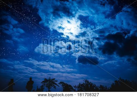 Attractive of amazing blue dark night sky with many stars and cloudy above silhouette of trees. Outdoor at nighttime with moonlight. Pretty nature use as background. Vivid colors.
