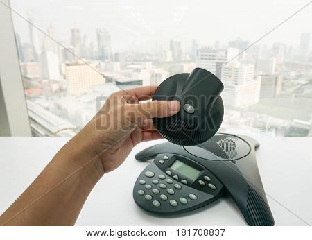close up businesswoman use conference IP phone for meeting with Regional team